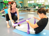 Asian woman doing exercise on gym floor with the help of a personal trainer.
